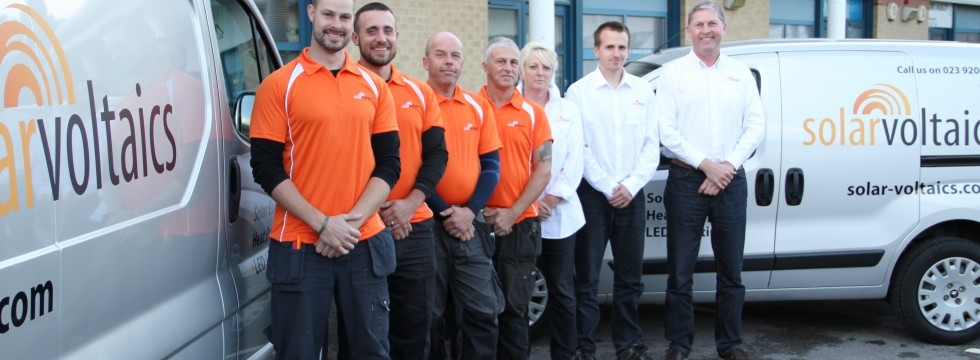 Solar Voltaics team photo - management and installation engineers in orange logo shirts - next to two of our vans
