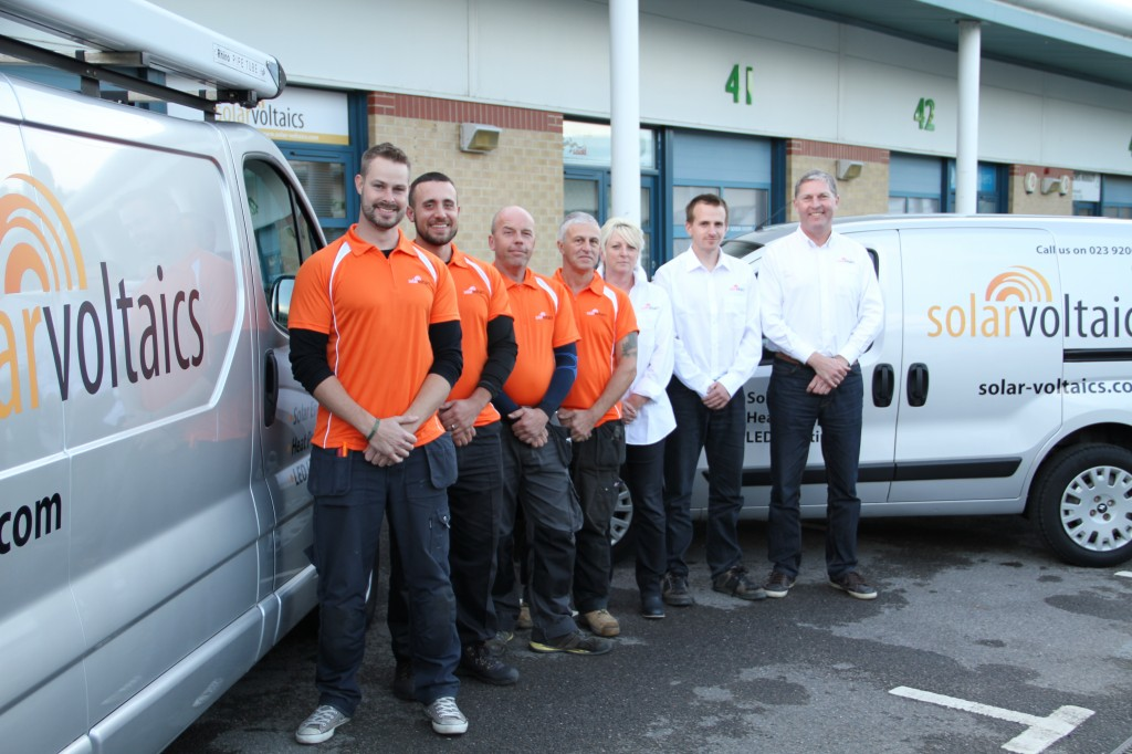 Solar Voltaics team photo - Solar PV Team and solar installation engineers in orange logo shirts - next to two of our vans